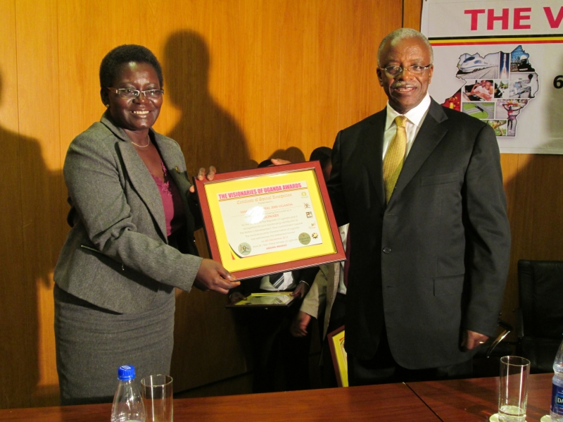 Rtn. Hon Prime Minister of Uganda, Amaama Mbabazi handing over the award to the Country Director-SG2000, Dr. Roselline Nyamutale
