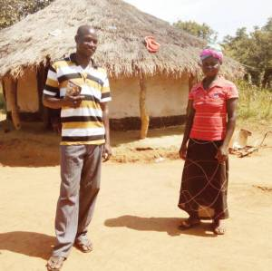 Before and after: Tonny and wife standing in front of their old house (left), and the new house (right) they have been able to build thanks to the Sasakawa Africa Association.