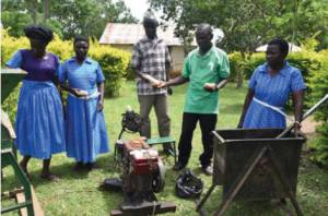 Chairperson Otwani Terensio (middle), Hellen Epuruge (far right) and other members of the Nyarakot Group showcasing their machines.